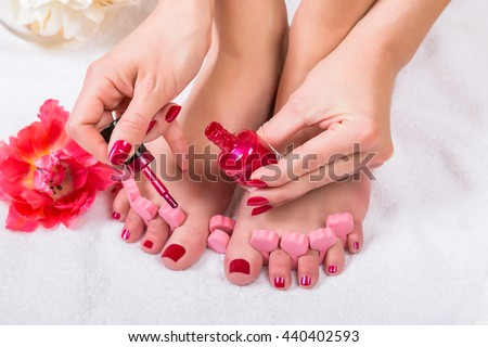 Woman with manicured fingernails painting her toenails with red varnish from a bottle in a beauty concept, close up on her hands and feet and a fresh red tulip alongside - stock photo