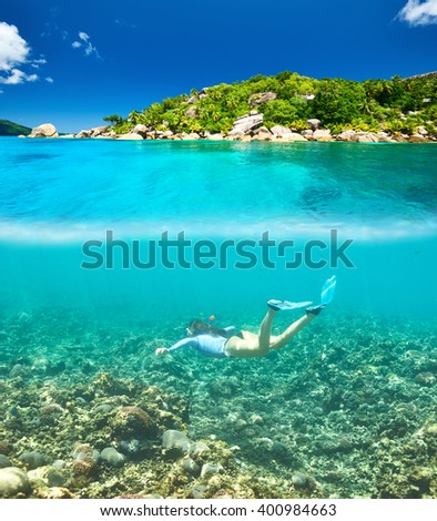 Woman with mask snorkeling in clear water at Seychelles - stock photo