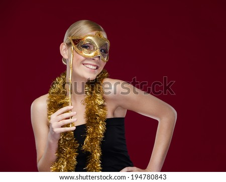 Woman with masquerade mask and tinsel, isolated on purple - stock photo