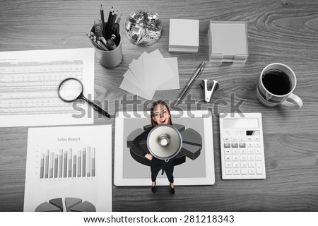 Woman with megaphone on office table. Desk office financial accounting graphs analysis - stock photo