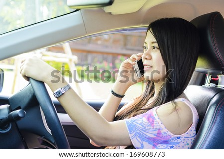 Woman with mobile phone in the car while driving. - stock photo