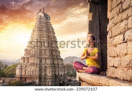 Woman with Namaste mudra sitting near Virupaksha temple in Hampi, Karnataka, India - stock photo