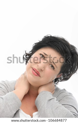 Woman with neck pain standing with her head tilted and hands behind her head as she stries to stretch to relieve the tension and stress - stock photo