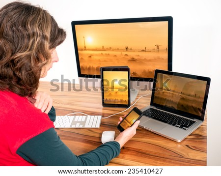 Woman with networked computers and mobile devices - stock photo