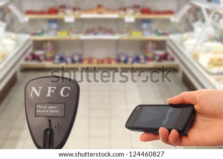 Woman with NFC mobilephone paying in a supermarket - stock photo
