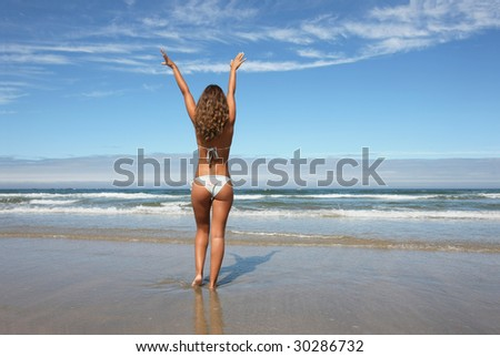 woman with open arms in the beach - stock photo