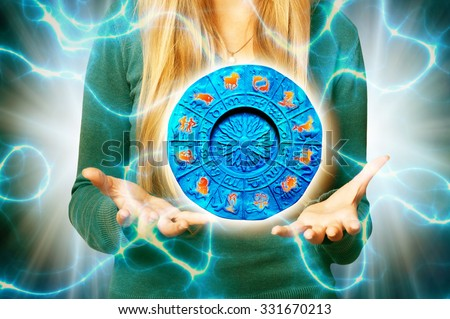 woman with open hands holding a zodiac plate with astrology signs - stock photo