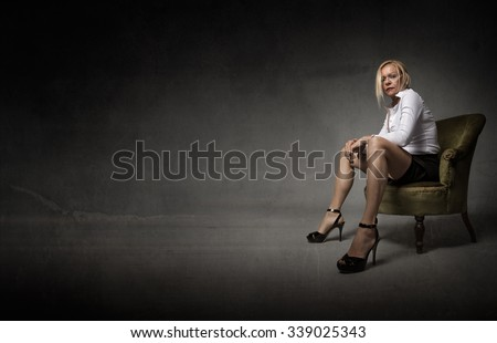 woman with open legs sitting on green sofa, dark background - stock photo