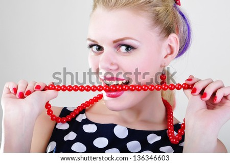 Woman with open mouth, makeup and white teeth beating red chaplet - stock photo