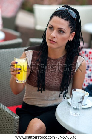woman with orange juice in outside bar - stock photo