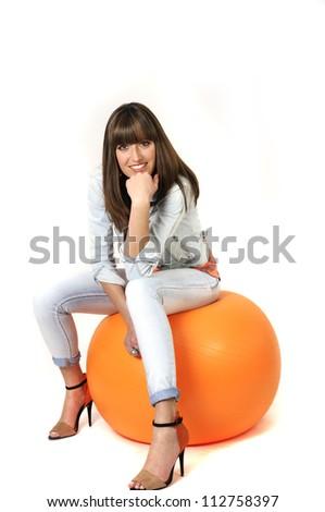 Woman with orange pilates ball concept shot. - stock photo