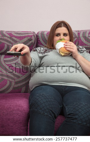 Woman with overweight eating a burger and watching tv - stock photo