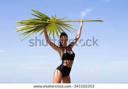 Woman with palm branch on beach in swimsuit near sea enjoying sun. Hair up.Tropics.Hot summer day.Sexy girl.Vacation.Photo from Phuket island. Thailand - stock photo