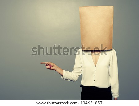 woman with paper bag on the head pointing at something over dark background - stock photo
