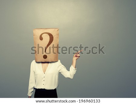 woman with paper bag pointing at something over dark background - stock photo
