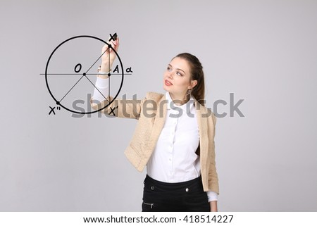 Woman with pen draws geometric shapes on grey background - stock photo