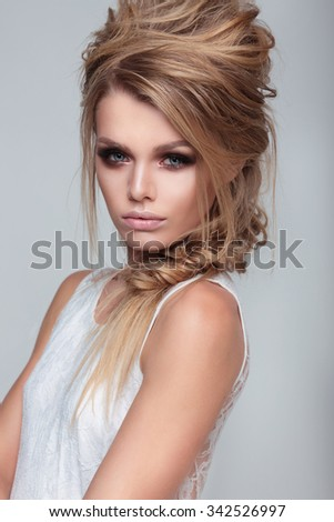 Woman with perfect skin wearing smoky make-up and hairstyle. - stock photo