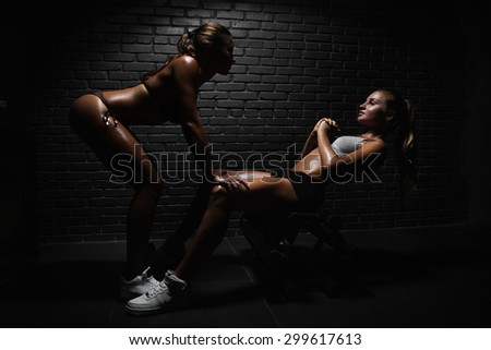 Woman with personal trainer doing sit ups in gym - stock photo