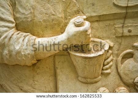 Woman with pestle and mortar in hands. Stone relief - stock photo