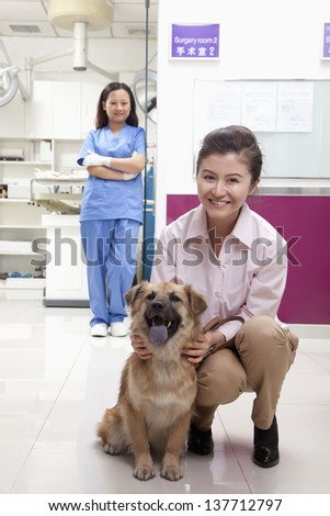 Woman with pet dog in veterinarian's office - stock photo