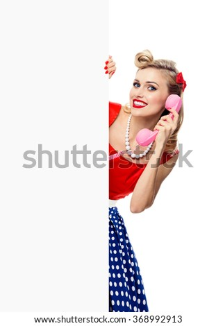 Woman with phone, in pin-up style dress, showing blank signboard with copyspace area for slogan or text, isolated. Caucasian blond model posing in retro fashion and vintage concept studio shoot. - stock photo