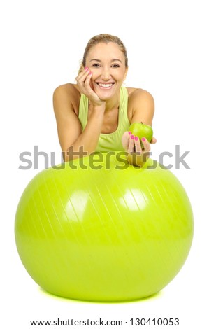 woman with pilates ball and an apple isolated in white - stock photo