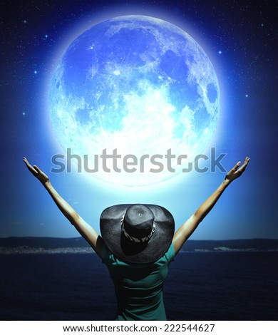 Woman with raised hands facing a wave and full moon. Elements of this image furnished by NASA.  - stock photo