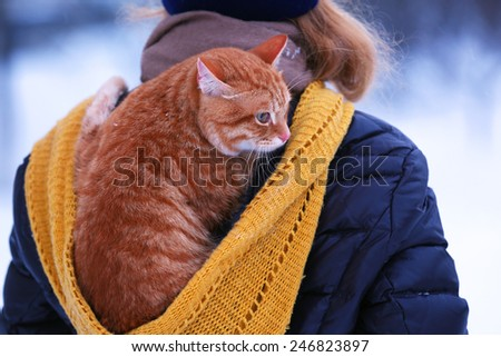 Woman with red cat on her back with snowfall background - stock photo