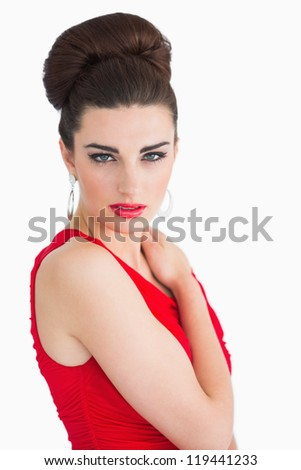 Woman with red dress touching her shoulder and looking at camera - stock photo