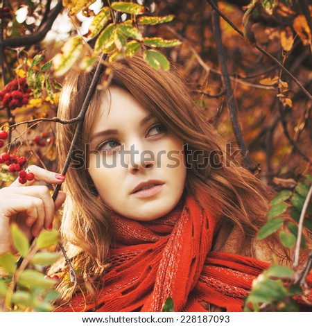 Woman with red hair and scarf outdoors - stock photo