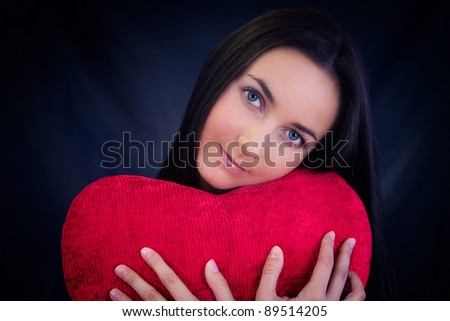 Woman with red heart shaped cushion on dark background - stock photo