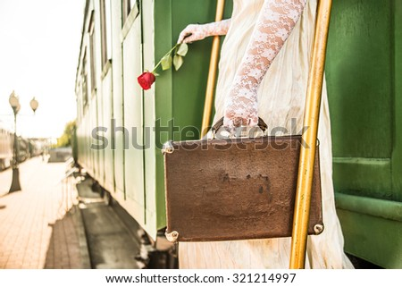 Woman with red rose  sit on stair of wagon. Railway station against retro vintage old locomotive in perspective. Young adult girl hold in hands one flower and read book Female wear gloves and dress  - stock photo