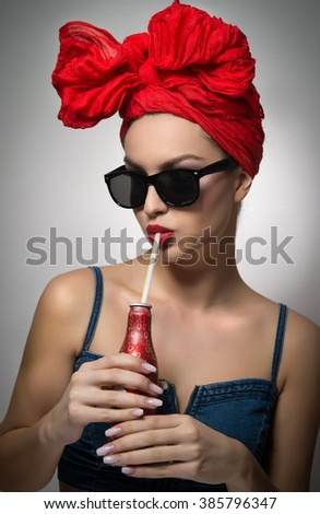 Woman with red turban and sunglasses drinking from a bottle with a straw. Attractive girl portrait holding a bottle, studio shot on gray background. Happy young female, advertisement concept - stock photo