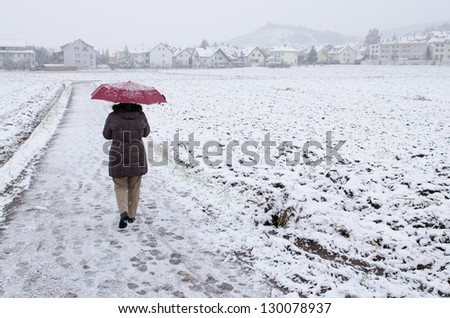 Woman with red umbrella is strolling in the snow - stock photo
