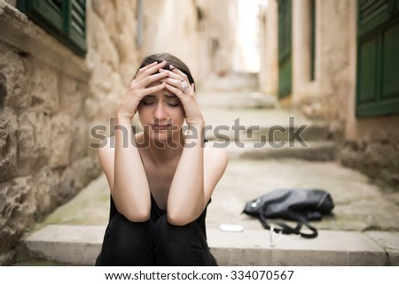 Woman with sad face crying.Sad expression,sad emotion,despair,sadness.Woman in emotional stress and pain.Woman sitting alone on the street with her things thrown on the street - stock photo