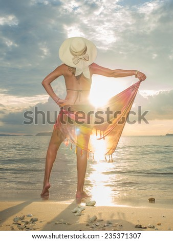 Woman with sarong on the beach at sunset in Thailand - stock photo
