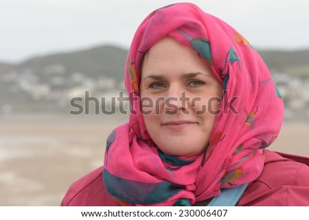 Woman with scarf wrapped around head on autumn day - stock photo