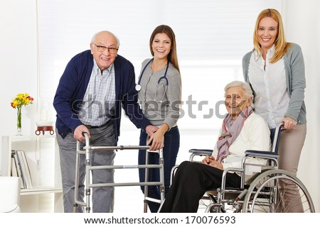 Woman with senior couple at home getting help from a caregiver - stock photo