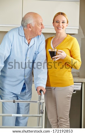 Woman with senior man and his walker in the kitchen - stock photo