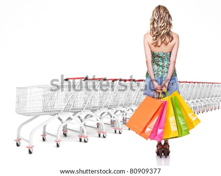 woman with shopping bag and trolley cart background - stock photo