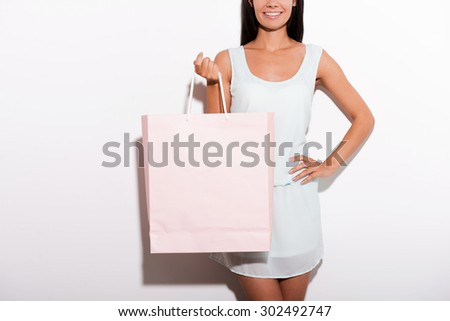 Woman with shopping bag. Cropped image of cheerful young woman in dress standing against white background and carrying shopping bag - stock photo