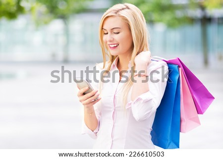 Woman with shopping bags and mobile phone  - stock photo