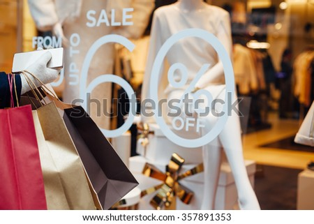Woman with shopping bags and mobile phone in front on store window with copy space - stock photo