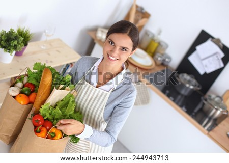 Woman with shopping bags in the kitchen at home, standing near desk - stock photo