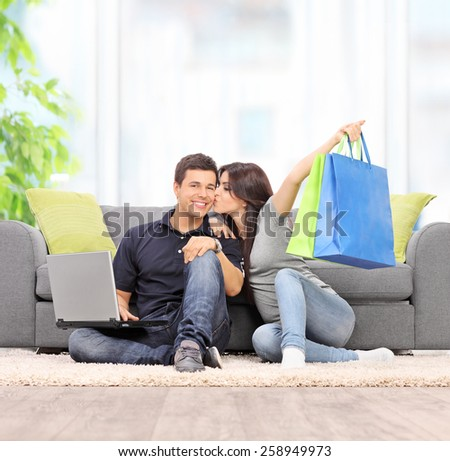 Woman with shopping bags kissing her boyfriend seated by a sofa at home shot with tilt and shift lens - stock photo