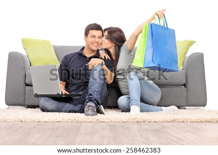 Woman with shopping bags kissing her boyfriend seated by a sofa isolated on white background - stock photo