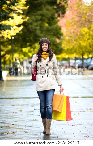 Woman with shopping bags walking in autumn. Fashion female shopper outside. - stock photo