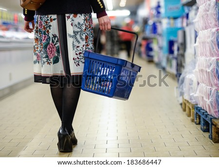 woman with shopping basket in the supermarket - stock photo
