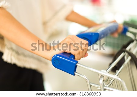 Woman with shopping cart. - stock photo