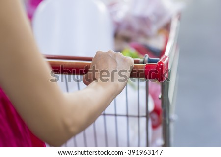 Woman with shopping cart in supermarket. - stock photo